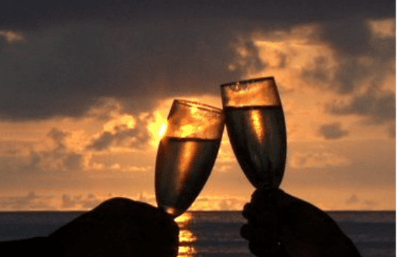 Two wine glasses clinking at sunset.